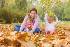 Happy Family Autumn. Happy Family Mother with two Daughters enjoying the autumn in the park.Carefree Relax Fall Concept royalty free stock photos
