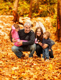 Happy family in autumn park. Photo of happy family in autumn park, parents with cheerful babies playing in fall forest, mother and father with daughter and son Stock Images