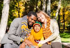 Happy family in autumn park. African American family: black father, mom and child boy on nature in fall. Happy family in autumn park. African American family Stock Image