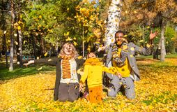 Happy family in autumn park. African American family: black father, mom and child boy on nature in fall. Happy family in autumn park. African American family Stock Images