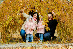 Happy family in autumn in the park. Parents with two children are twins in nature Stock Photo