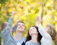 Happy family in autumn park. Happy family having fun outdoors in autumn park against blurred leaves background Stock Photo