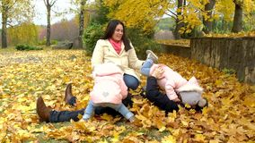 Happy family in autumn park. Mother, father and two little girls stock video footage