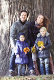 Happy family in autumn park. Near big tree trunk Stock Photos