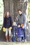 Happy family in autumn park. Near big tree trunk Royalty Free Stock Photography