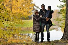 Happy family in autumn park near lake.  Royalty Free Stock Image