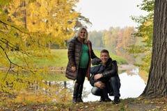 Happy family in autumn park near lake Stock Image