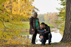 Happy family in autumn park near lake.  Stock Image