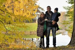 Happy family in autumn park near lake Stock Photos