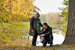 Happy family in autumn park near lake Stock Photos