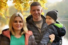 Happy family in autumn park near lake Stock Photo