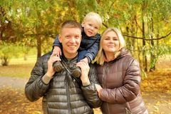 Happy family in autumn park. Near lake Stock Photos