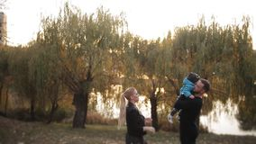 Young happy family with little son walking in autumn Park at sunset in the Park near the lake. stock video footage