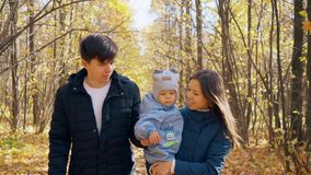 Happy family in autumn park. Parents with the child walk in the park. 4k stock video footage