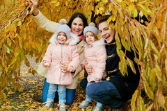Happy family in autumn in the park. Parents with two children are twins in nature Royalty Free Stock Images