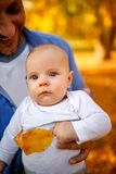 Happy family in the autumn park - portrait of baby boy with his stock images
