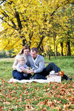 Happy family in autumn park. Reading a book Royalty Free Stock Images