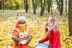 Happy family in autumn park. Happy family smiling and holding autumn leaves, focus om mother stock photography
