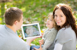 Happy family in autumn park. Happy family using tablet PC outdoors in autumn park against blurred leaves background Stock Image
