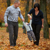 Happy family in autumn park. On yellow leaves Royalty Free Stock Images