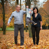 Happy family in autumn park. On yellow leaves Royalty Free Stock Photography