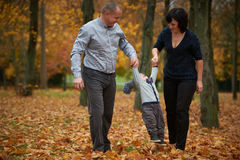 Happy family in autumn park. On yellow leaves Royalty Free Stock Photo