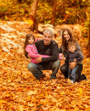 Happy family in autumnal forest Royalty Free Stock Photo