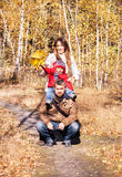 Happy family is in the autumnal park. Royalty Free Stock Photography