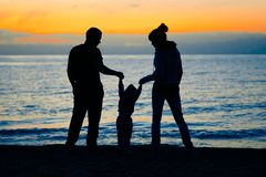 Family at sunset by the sea royalty free stock image