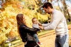 Happy family with baby boy in autumn park Stock Photos