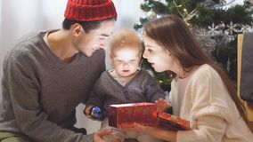 Happy Family and Baby with Christmas Gift near the Christmas Tree at home. Child opening a Gift Box. stock video