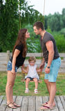 Happy family . The baby daughter rides a swing. Royalty Free Stock Images