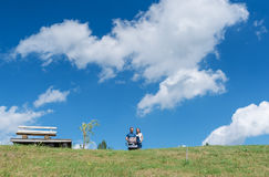Happy family with baby on the field. Green field under the blue sky. Summer landscape stock photos