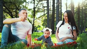 Happy family with baby girl spending time in summer park blowing soap bubbles stock video