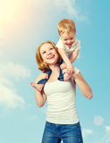 Happy family. baby sits astride the shoulders of the mother and. Laughing on blue sky background Stock Photography