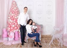 Family New Year`s concept. Mom and Dad are holding their baby. Happy family on the background of bright festive decorations, waiting for the holiday Royalty Free Stock Photo