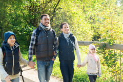 Happy family with backpacks hiking in woods Royalty Free Stock Image