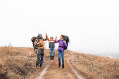 Happy family with backpacks holding hands stock photo