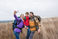 Happy family with backpacks taking selfie Stock Images