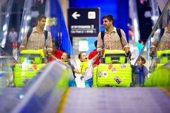 Happy family with baggage on conveyor in airport, ready to travel Royalty Free Stock Photography