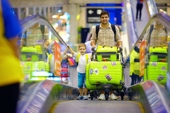 Happy family with baggage on conveyor in airport, ready to travel Royalty Free Stock Photo