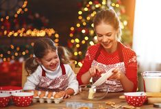 Happy family bake christmas cookies. Happy funny mother and child bake christmas cookies royalty free stock images