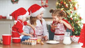 Happy family bake christmas cookies. Happy funny mother and children bake christmas cookies royalty free stock photo