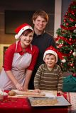 Happy family baking christmas cake together. Happy parents with small child baking christmas cake together, smiling at camera Stock Image