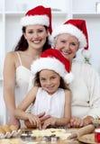 Happy family baking Christmas cakes stock photo