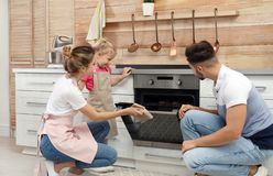 Happy family baking cookies in oven royalty free stock photo