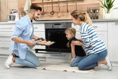 Happy family baking cookies in oven stock photos
