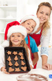 Happy family baking gingerbread cookies. Happy family at christmas time baking gingerbread cookies Royalty Free Stock Photography