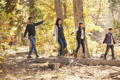 Happy family balancing on a fallen tree in a forest Stock Image