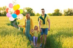 Happy family with balloons in field on sunny day. Happy family with colorful balloons in field on sunny day Stock Photo
